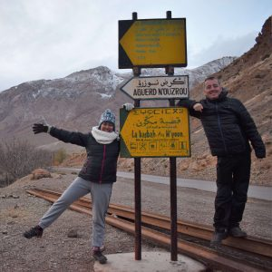 Mountains, snow, road, two people posing in front of a signage
