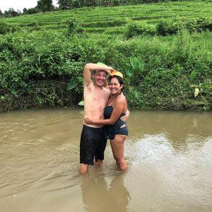 A man and woman posing, Green grass, muddy water