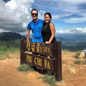 A man and woman posing in front of the Phu Chi Fa signs, mountains, blue sky with clouds