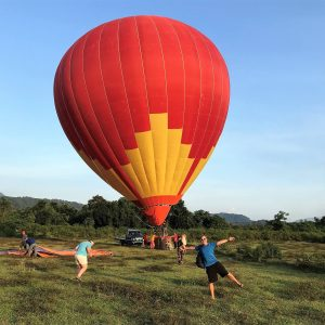Hot air balloon, people posing, blue sky, green grass and trees,