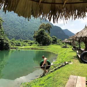 Mountains, Lagoon trees, green grass, man holding a tire, huts