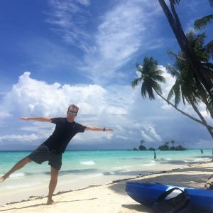 A man posing, blue sky with clouds, island, white sand, clear blue ocean, coconut trees