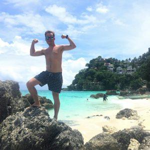 A man flexing, beach, blue sky with clouds, Island, white sand, clear blue ocean, rocks, beach houses
