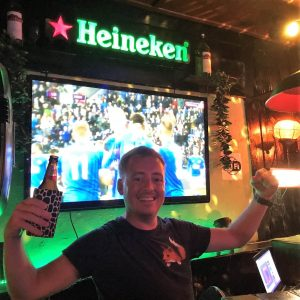 A man smiling while holding a beer, football streaming, heineken logo