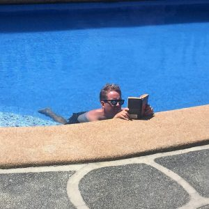 A man reading a book in a swimming pool
