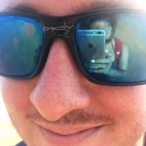 A man wearing sunglasses , reflection of a woman taking the picture