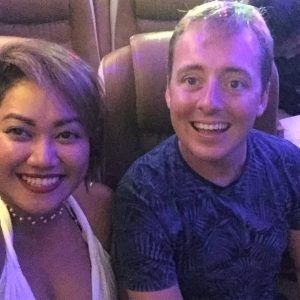 A couple smiling, riding a bus