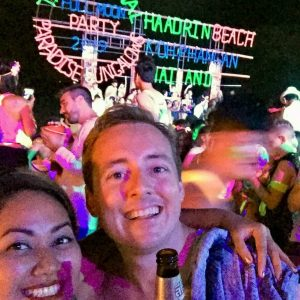Full moon party, people partying, neon glowing signs