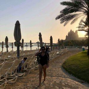 The Palm Jumeirah Dubai ,Sunset, beach, white sand, trees, green grass, beach chairs and umbrellas, people in swim wears