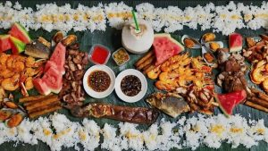 Foods on top of banana leaves, rice, shrimp, fish, grilled pork, mussels, watermelon, coconut, sauces, vegetables