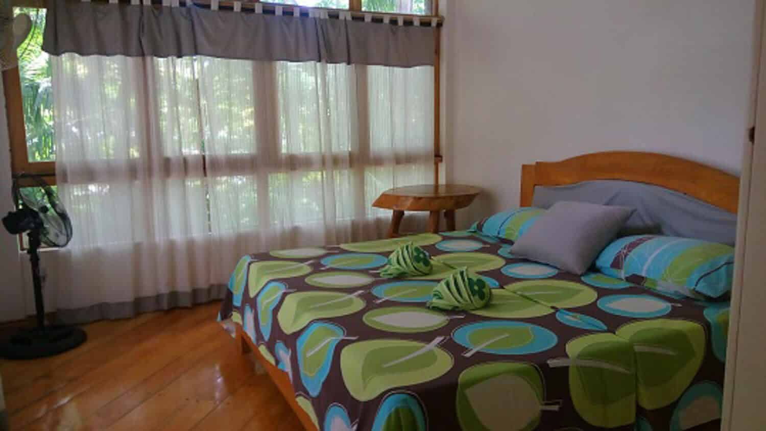 Bed, Nightstand, Windows with curtains, Electric Fan