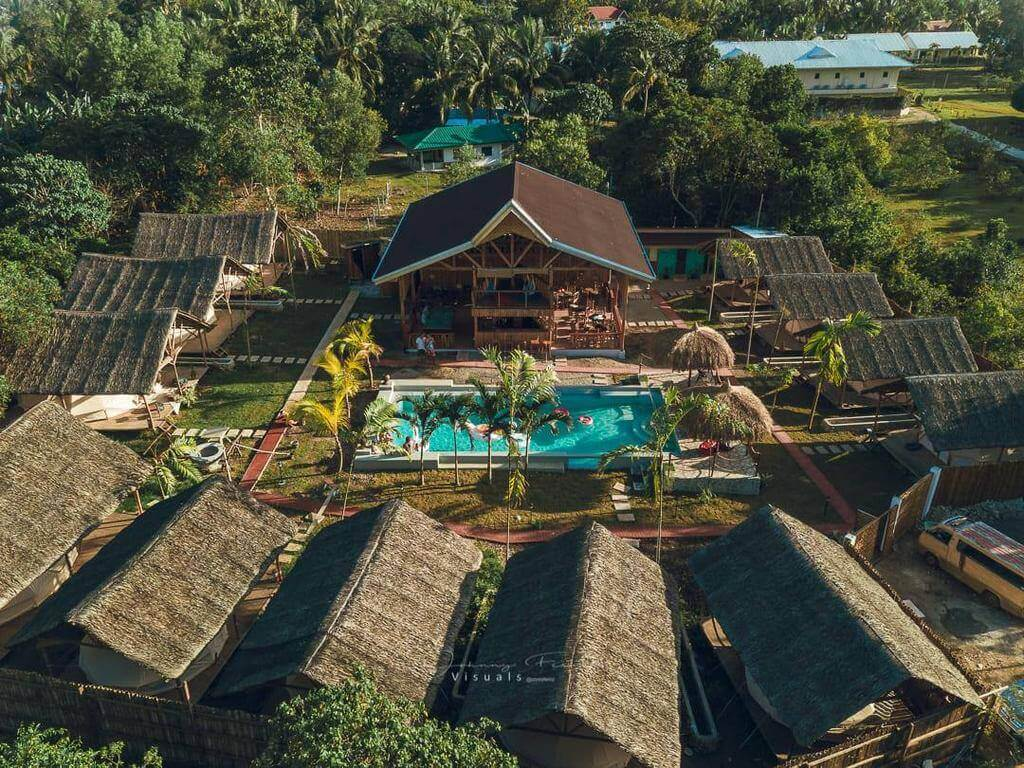 Glamping Aerial View, Swimming Pool, beach Houses, Trees, coconut Trees, Green Grass, Cottages