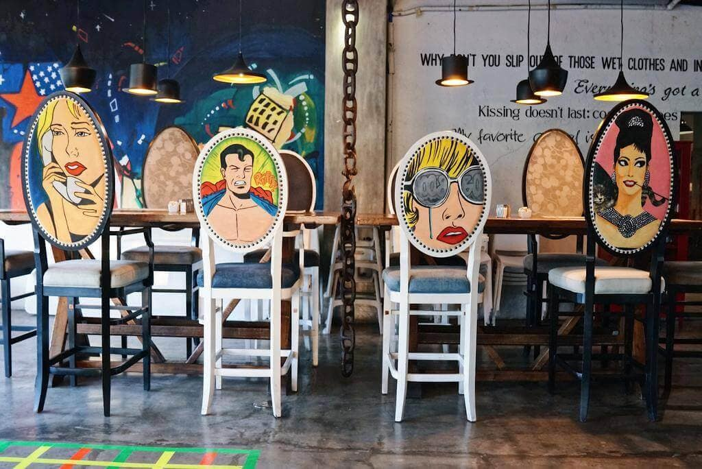Table, Chairs With Pop Arts Designs, Hanging Lights, Painted Wallpapers