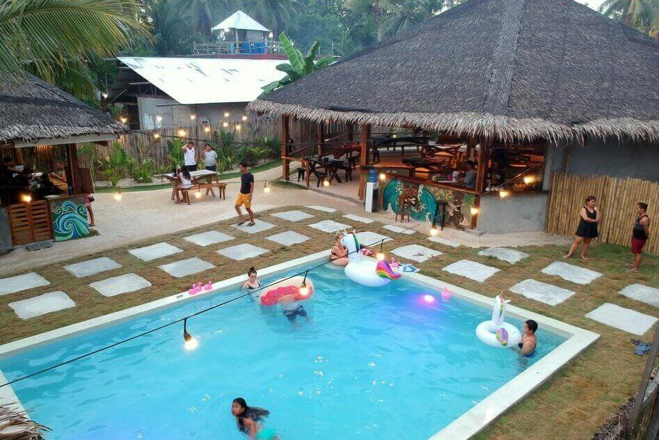Coconut trees, Huts, Cpttages, Swimming Pool, People hanging out