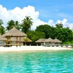 Beach, ble sky with clouds, trees, white sand, clear blue ocean, huts, coconut trees