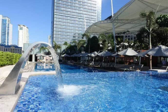 Swimming pool, Beach Umbrellas, Palm trees, Bushes, Buildings,