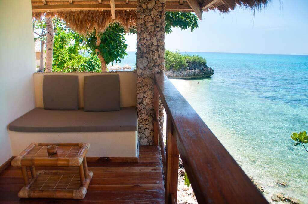 Balcony, Sofas, Table, Ocean, White Sand, Trees, Rocks