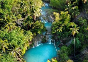 Waterfalls, coconut trees, luscious green trees, clear blue waters