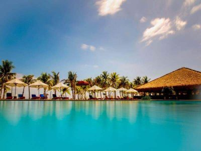 Huts, Beach chairs and umbrellas, blue sky, coconut trees, swimming pool